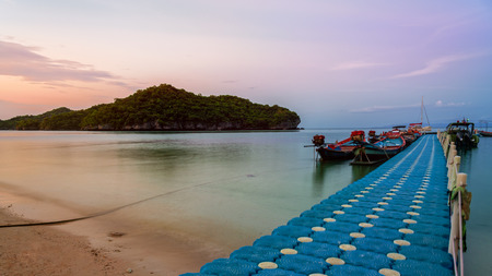 Floating bridge pier for tourist on the beach in front of Ko Wua Ta Lap island view Ko Phi during sunset at Mu Ko Ang Thong National Marine Park in Gulf of Thailand, Surat Thani province,16:9 widescreen