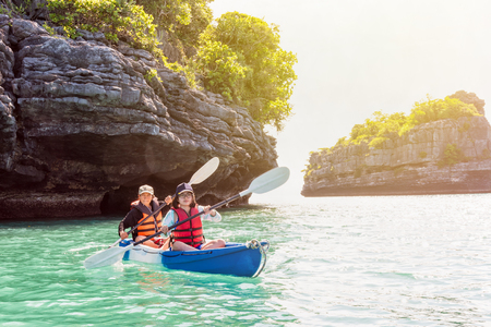 Two women are mother and daughter. Travel by boat with a kayak on the sea under sunlight at summer around Ko Phi enjoy the beautiful nature of the sea and island, Mu Ko Ang Thong National Park, Surat Thani, Thailand