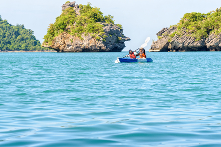Two women are mother and daughter. Travel by boat with a kayak around island enjoy view the beautiful natural landscape of the blue sea at summer, Mu Ko Ang Thong National Park, Surat Thani, Thailand