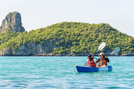 Two women are mother and daughter. Happy family travel by kayak around Ko Mae Ko view the beautiful nature of the sea and island during summer at Mu Ko Ang Thong National Park, Surat Thani, Thailand