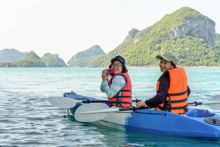 Two women are mother and daughter using a camera take pictures on kayak while travel by boat with happy on the sea during summer at Ko Wua Ta lap islands in Mu Ko Ang Thong National Park, Surat Thani, Thailand