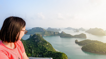 Woman tourist on peak view point of Ko Wua Ta Lap island looking beautiful nature landscape during sunrise over the sea in Mu Ko Ang Thong National Park, Surat Thani, Thailand, 16:9 widescreen Stock Photo