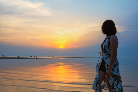 Young woman are standing watching the beautiful natural landscape, colorful of the sky and the sea during a sunset on the beach at Nathon Sunset Viewpoint in Ko Samui island, Surat Thani, Thailand Stock Photo