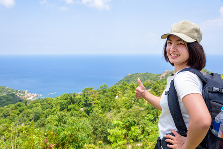 Women tourist with a backpack wear cap raise thumbs up for the beautiful nature landscape blue sea and sky from high scenic viewpoint at Koh Tao, Surat Thani, Thailand Zdjęcie Seryjne