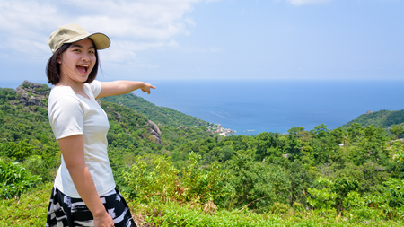 Women tourists pointing the finger at the sea and open mouth on high viewpoint to see the beautiful nature landscape of Koh Tao island is a famous attractions in Surat Thani, Thailand, 16:9 widescreen