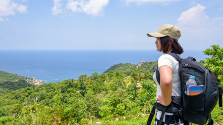 Women tourist with a backpack wear cap standing look at beautiful nature landscape blue sea and sky from high scenic viewpoint at Koh Tao in Surat Thani, Thailand, 16:9 widescreen Stock Photo