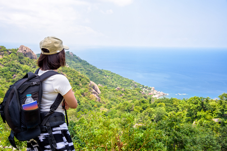Women tourist with a backpack wear cap standing look at beautiful nature landscape blue sea under the summer sky from high scenic viewpoint at Koh Tao in Surat Thani, Thailand Zdjęcie Seryjne