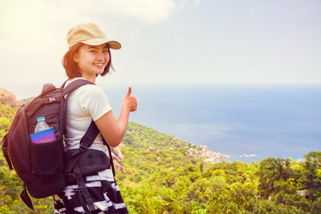 Vintage style women tourist with a backpack wear cap raise thumbs up for the beautiful nature landscape blue sea and sky from high scenic viewpoint at Koh Tao, Surat Thani, Thailand Zdjęcie Seryjne
