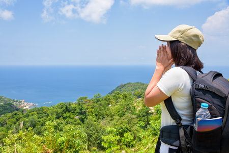 Women tourist with a backpack wear cap raise hand at the mouth yelling and beautiful nature landscape blue sea and sky from high scenic viewpoint at Koh Tao, Surat Thani, Thailand Zdjęcie Seryjne