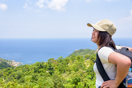 Women tourist with a backpack wear cap standing happily look at beautiful nature landscape blue sea and sky from high scenic viewpoint at Koh Tao in Surat Thani, Thailand