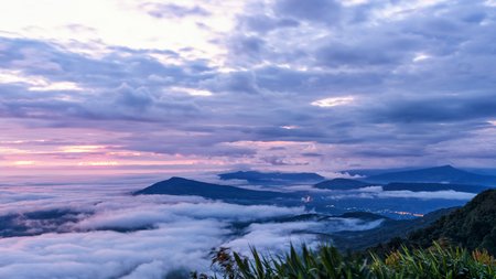 Beautiful nature landscape of the fog covers the summit and the colorful sky during sunrise in the winter, high angle view from the viewpoint of Phu Ruea National Park at Loei province, Thailand. Stock Photo