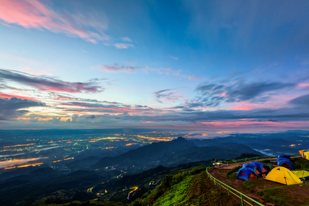 High view beautiful nature landscape of colorful sky during the sunrise, see the lights of the road and city from the campsite at Phu Thap Berk viewpoint, Phetchabun Province, Thailand Foto de archivo
