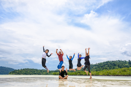 Asian traveler group adult and teens are family, Happy life enjoy by play jumping together at the beach on blue sky background, vacation in summer holiday at Ko Lipe and Ra Wi island, Tarutao, Thailand