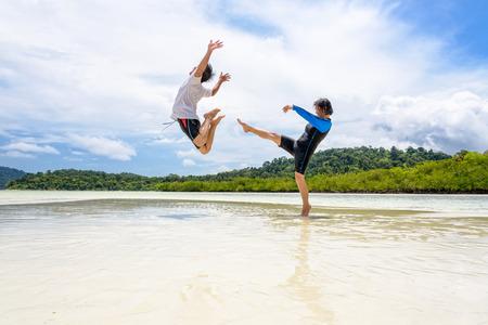 Happy asian couple play fun activity together woman show the teasing position, kicking a man to bounce far away on the beach of Ko Ra Wi near Ko Lipe island, Tarutao National Park, Satun, Thailand