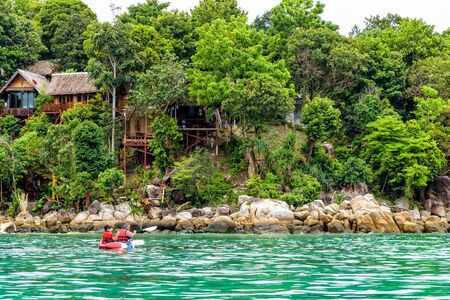 Two tourists are father and daughter travel by boat with a kayak in summer at front the resort on island of Ko Lipe enjoy the beautiful nature the sea in morning, Tarutao National Park, Satun, Thailand