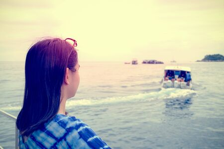 Back of Asian woman looking at the speed boat that sailed away from her, With a lonely, solitary, sad atmosphere during sunset in vintage style