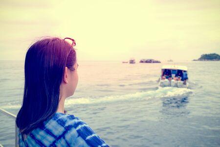 Rückseite einer asiatischen Frau, die das Schnellboot betrachtet, das von ihr weggefahren ist, mit einer einsamen, einsamen, traurigen Atmosphäre bei Sonnenuntergang im Vintage-Stil