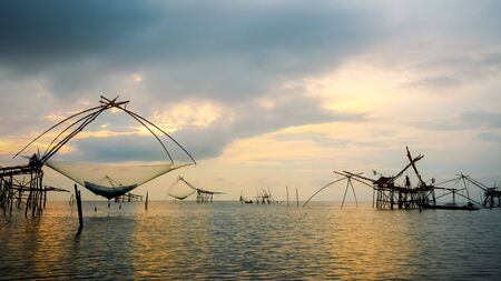 Beautiful nature landscape of Songkhla Lake at sunrise and fisherman are using bamboo and net as native fishing tool to catch fish rural lifestyle at Pakpra canal, Baan Pak Pra, Phatthalung, Thailand