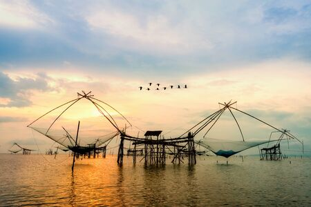 Beautiful nature landscape golden light of the morning sky at sunrise with flock of birds are flying over the native fishing tool, rural lifestyle at Pakpra canal, Baan Pak Pra, Phatthalung, Thailand Stock fotó