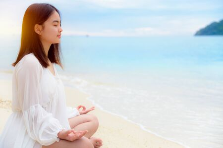 Beautiful asian young woman practice yoga on the beach near the sea under sunlight at sunrise, Relaxation for health in the midst of nature with happiness and peace, blank for the background 版權商用圖片