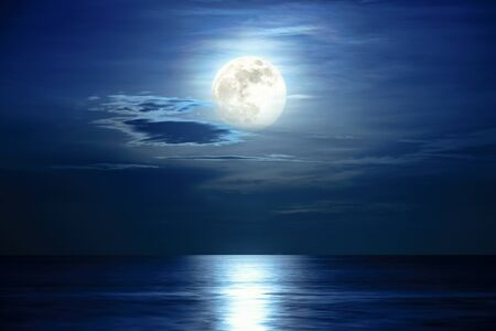 Super full moon and cloud in the blue sky above the ocean horizon at midnight, moonlight reflect the water surface and wave, Beautiful nature landscape view at night scene of the sea for background Stock Photo
