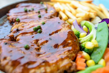 Close up of food made from grill meat, Beef steak topped with black pepper sauce on a hot plate, Dinner with vegetable salad and french fries Stock fotó