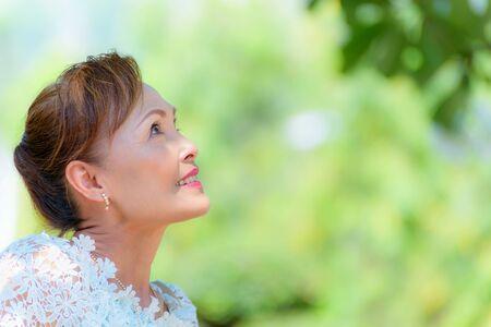 Nahaufnahmeseitengesicht eines gesunden asiatischen Frauenkleides mittleren Alters in thailändischer Kleidung, Porträt alte Dame, die draußen ruht und glücklich im Park lächelt, Kopienraum auf grünem Baumnaturhintergrund
