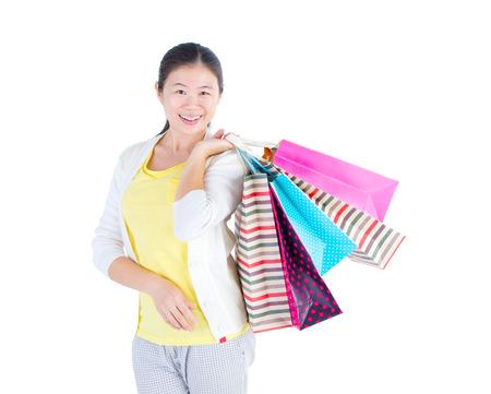 shopper: Pretty asian shopper holding shopping  bags.