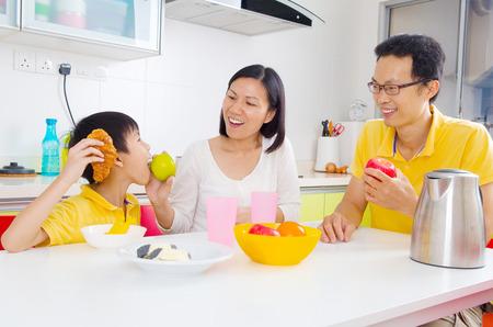 niños desayunando: familia feliz e hijo que comen las frutas en la cocina Foto de archivo