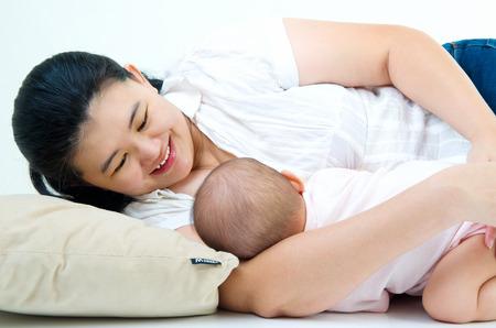 lactancia materna: Mujer asiática que amamanta a su bebé Foto de archivo