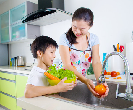 ni�os ayudando: Asia madre e hijo en la cocina Foto de archivo