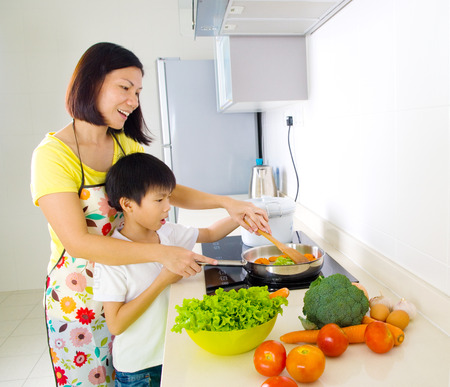 niños cocinando: Asia madre e hijo en la cocina Foto de archivo