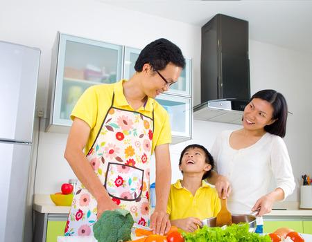 niños cocinando: Familia asiática preparación de verduras para cocinar en la cocina.