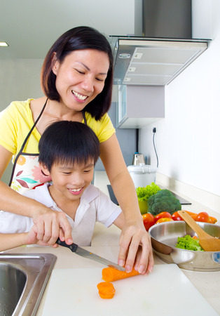 southeast asian: Asian mother and son cooking in the kitchen
