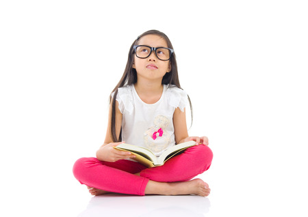 wearing spectacles: Asian girl wearing spectacles sitting on the floor with books Stock Photo