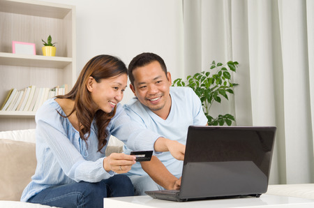 parejas: Asia pareja usando la computadora port�til para realizar compras en l�nea