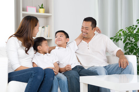 family indoors: Portrait of asian family sitting on sofa