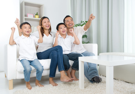 mujer viendo tv: Familia asi�tica ver la televisi�n y gritando en su equipo local en una competici�n deportiva Foto de archivo