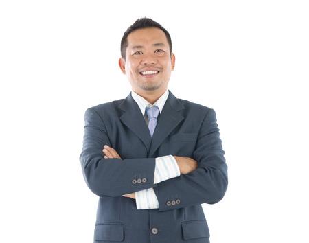 自信を持って東南アジア系のビジネスマンは、白い背景の上腕を交差