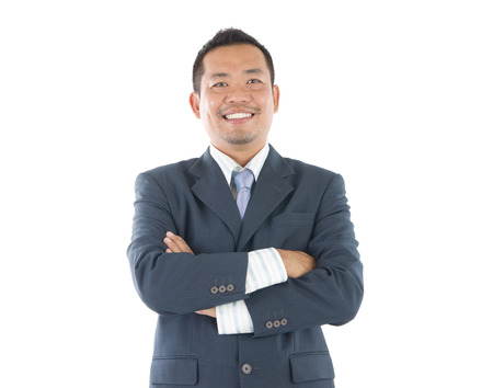 joyful businessman: Confident Southeast Asian businessman crossed arms over white background Stock Photo
