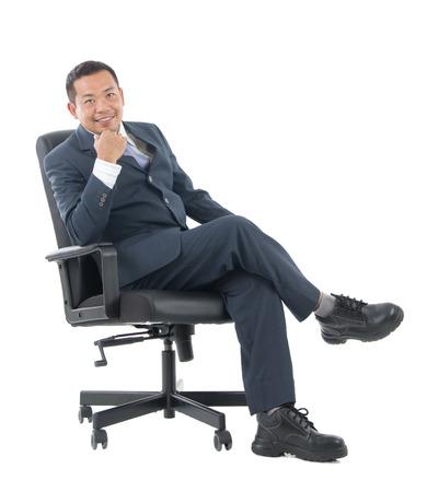 hombre sentado: el cuerpo del hombre de negocios de Asia plena sentado en la silla, con los brazos cruzados aislados sobre fondo blanco.