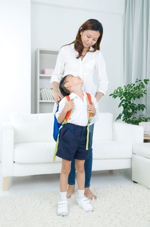 Asian mother get her son ready to school