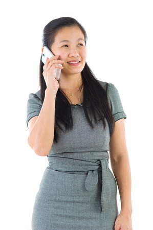 Southeast Asian business woman on smartphone communicatio Stock Photo