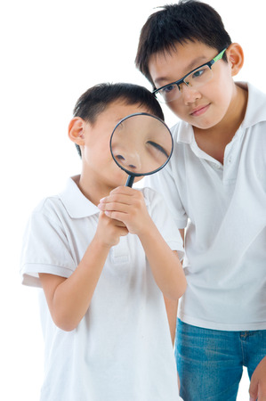 peers: A little chinese boy and his brother peers at the camera through a magnifying glass, isolated on white background