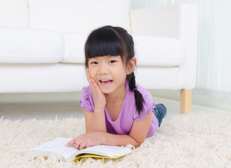 kids studying: Asian girl lying on the floor and reading Stock Photo