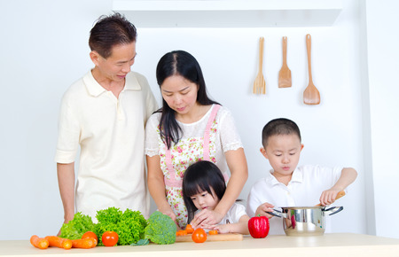 asian cooking: Asian family in the kitchen Stock Photo