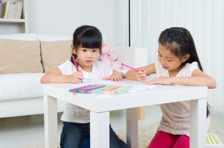 niños con lÁpices: Los niños asiáticos de dibujo
