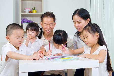 asian family: asian family doing school homework at living room Stock Photo
