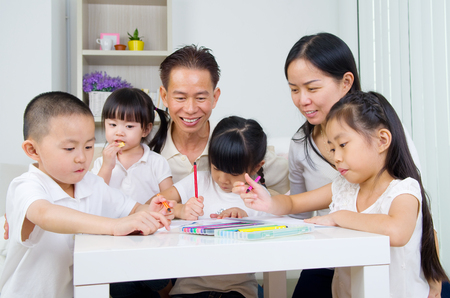 padre e hija: Familia asi�tica haciendo la tarea escolar en la sala de estar
