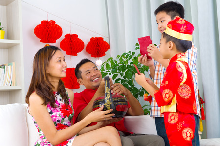 new look: Asian boys presenting gift basket to parents on chinese new year